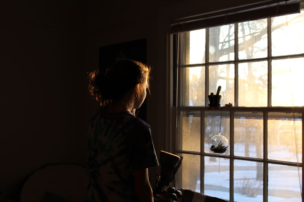 Women looking out of window, PTSD symptoms and treatment miss mental