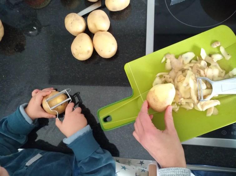 Kind hilft Kartoffeln schälen