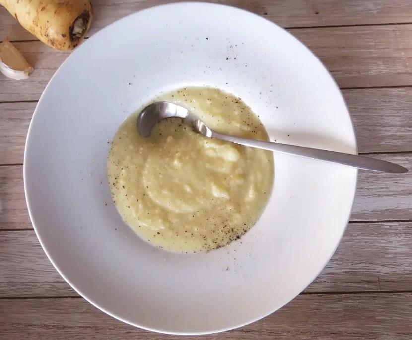 Weisse Karottensuppe in Teller, mit Löffel