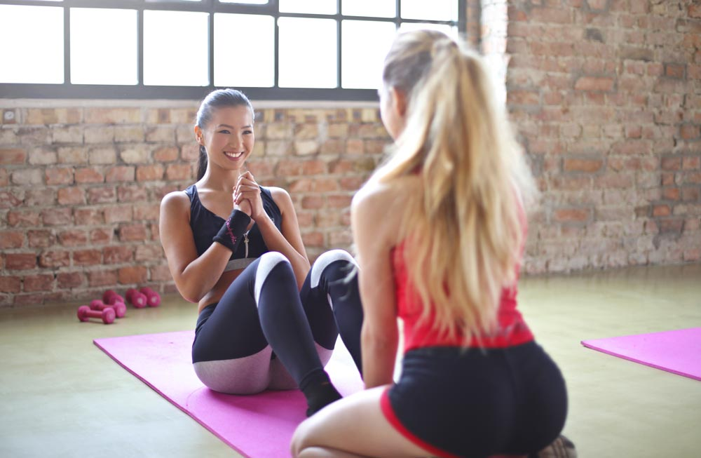 Women works out with partner at the gym smiling