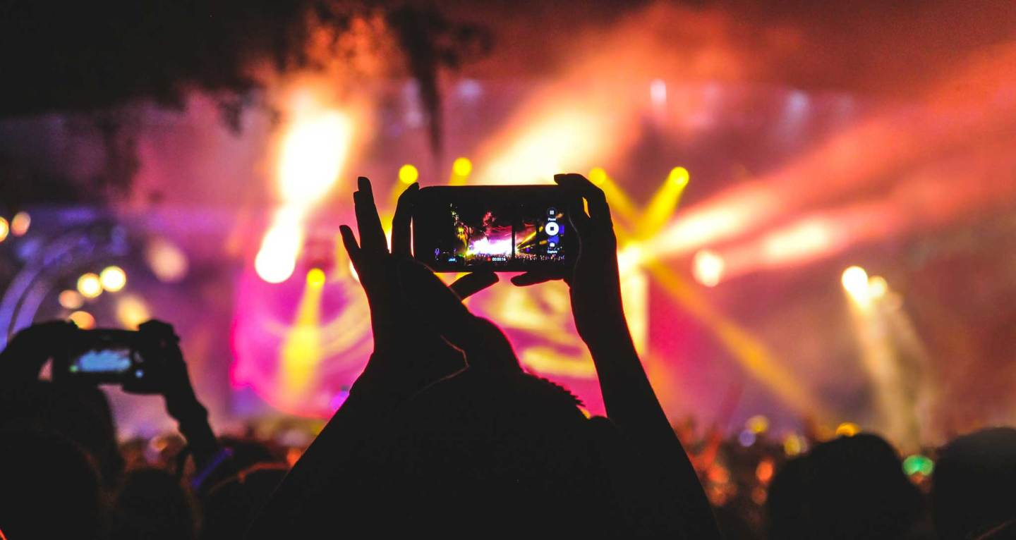 taking a photo at a concert — watching a concert through phone