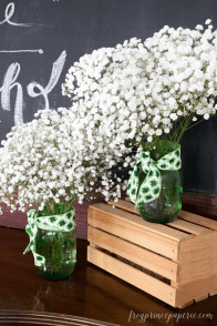 Baby's breath in bottle green vase and wrapped with a St. Patrick's inspired ribbon!