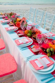 Baby blue and coral table setting on a beach! I love the level of detail in the exotic fruit centrepieces!