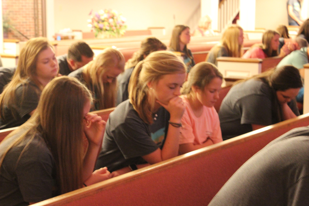 Students spending time in prayer at worship