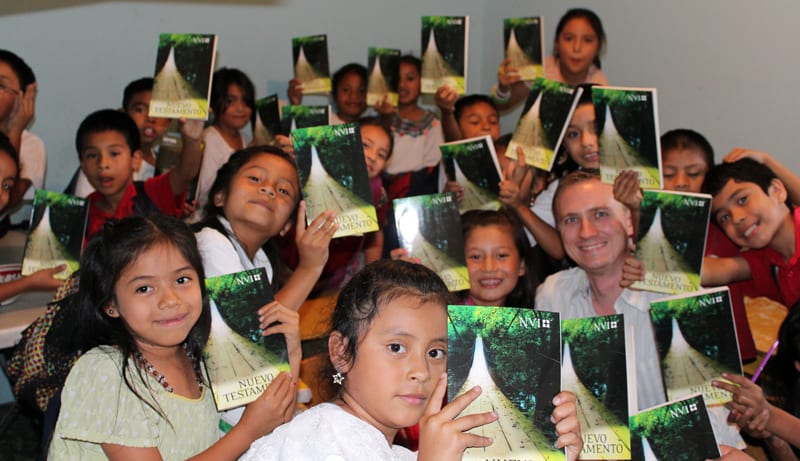 Timothy Martiny giving Bibles to the students at the Precious Moments School and Orphanage