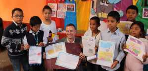 Tim receiving thank you cards from the children
