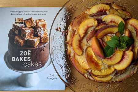 gâteau aux pêches sur une cloche près du livre Zoë Bakes