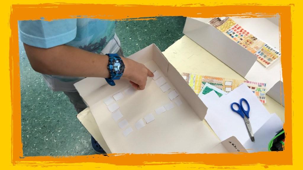Bambino che costruisce plastico aula.