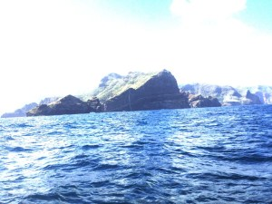 1. Joyful's view as she approached Nuku Hiva, the Marquises Archipelago's largest island.  The white limestone cross is near the East entrance to the harbor.