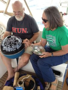 36. Bill held the NOAA drifter buoy as Anne painted the date, Joyful's name, the longitude & latitude, the names of Joyful's three schools & a Bible verse on the NOAA drifter buoy before its deployment southwest of the Galapagos Islands.