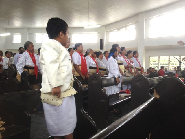 8. In the Free Wesleyan Church of Tonga, a young lad wears a Tongan sarong covered with the woven wrap signifying allegiance to the crown of Tonga. The choir in the background and most of the congregation also wore these traditional garments