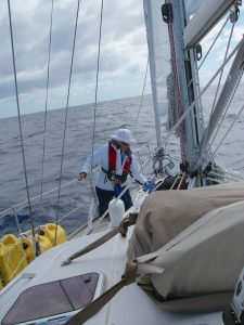 27. Flat Mr. Davis is always helpful aboard Joyful and on land. Here he is checking the lashings which secure the lightweight sail onto Joyful's foredeck when it is not being used. He proclaimed it is well secured