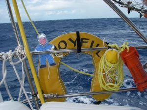 33. Flat Mr. Davis inspects Joyful's man overboard safety devices each day. The horseshoe life preserver is attached to a strobe light, a small drogue, and a 15 foot tall floating pole with a man overboard flag at the top
