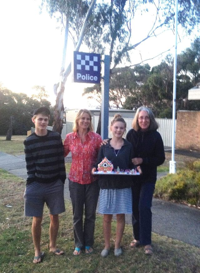131. Gabrielle, Beatrice, Josh and I stand in front of the police department on Phillip Island. Gabrielle chose to give the gingerbread house she made to the policemen for Christmas