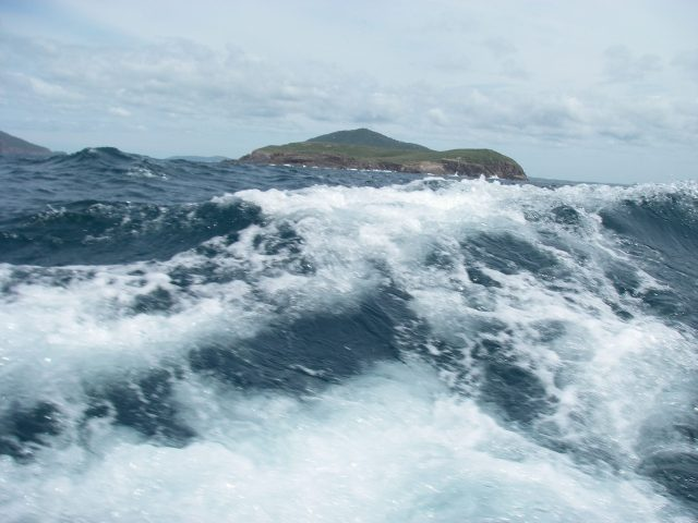 56.5. Joyful sailed closely to some of the islands to avoid certain contrary currents. I put the camera down low by Joyful's hull so you could see Joyful's bow wave up close!