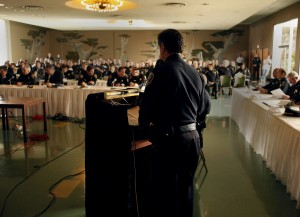Tacchini addresses a room packed with police