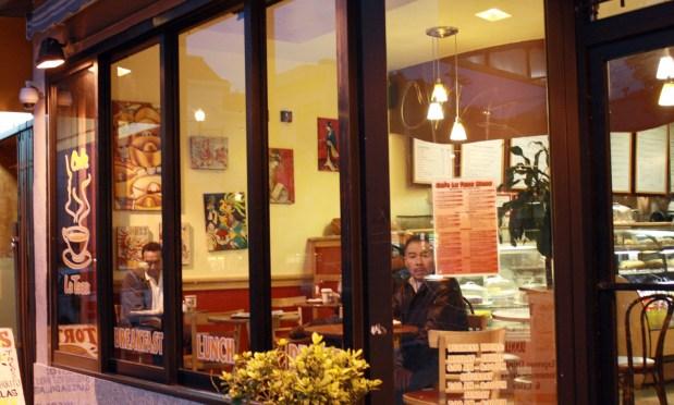 Enjoying coffee and newspaper inside La Taza Cafe.