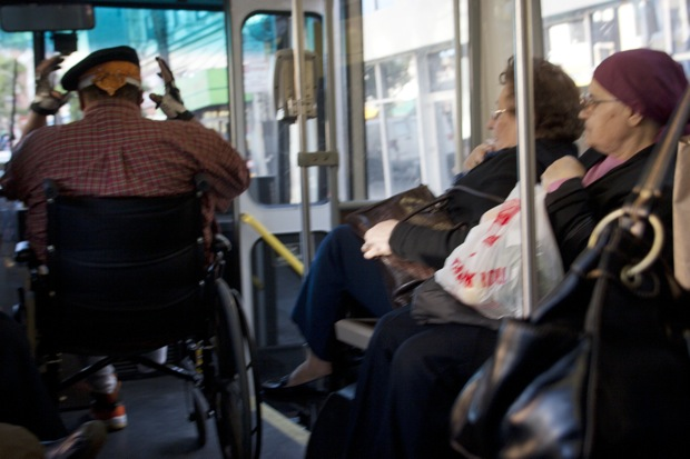 Making Room on the 40 Mission. Riders ift their legs to make room for a wheelchair user on the 49 Mission bus. File photo by Janis Lewin