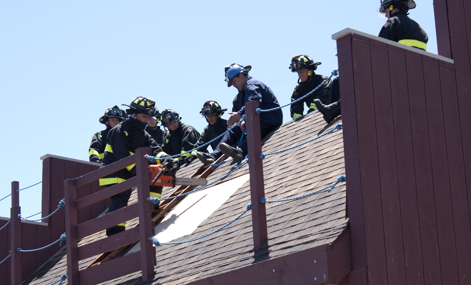 A group of firefighter cadets practice how to breach through a roof with a chainsaw.