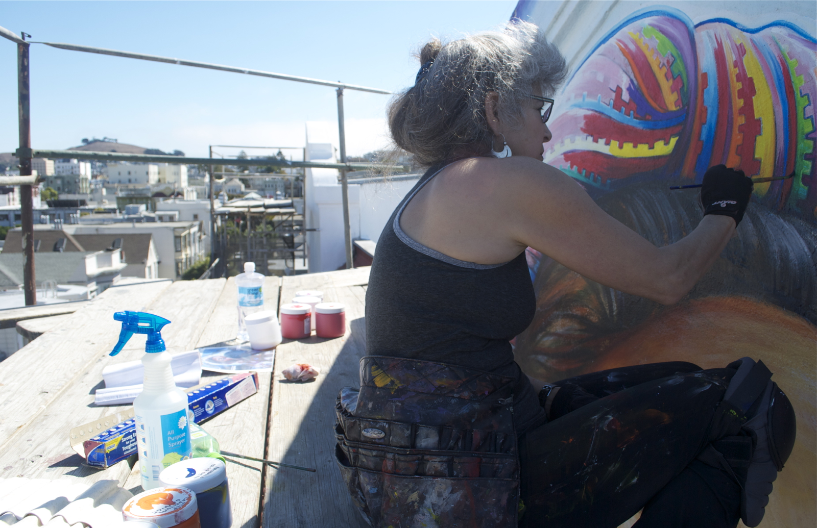 Artist Juana Alicia paints works to restore the mural on the Women's Building.