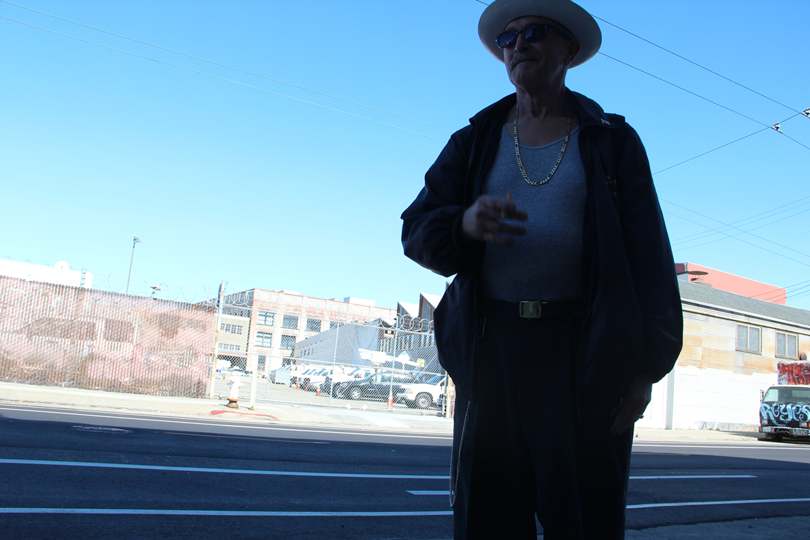 An older man stands against an urban backdrop and blue morning sky.