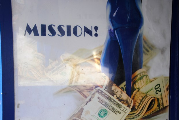 Image shows a blue stilleto standing on money