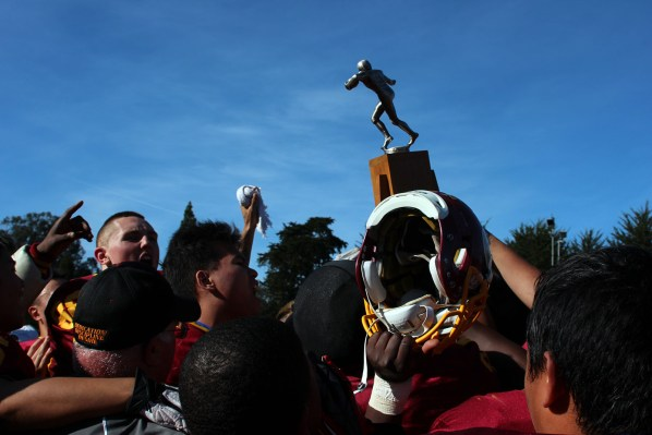 The Lincoln High School football team celebrates with the Turkey Day trophy after beating Mission High School on Thursday. It is the school's first tittle since 2008.