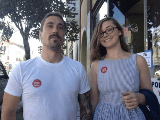 A young couple walks down Valencia street after voting