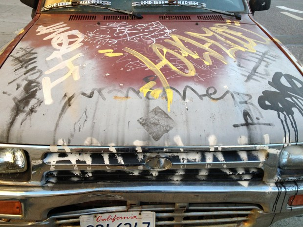 A car, covered in graffiti, parked at Folsom at 18th streets.