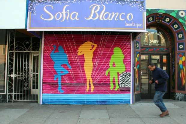 A man runs through the street in front of the Sofia Blanco Boutique on 21st and Mission.