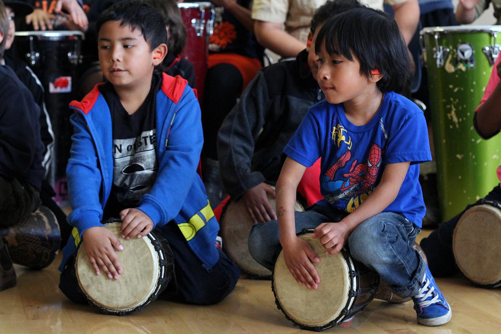 """Children drum as part of Loco Bloco's """"Hella Loco Carnaval"""" classes."""