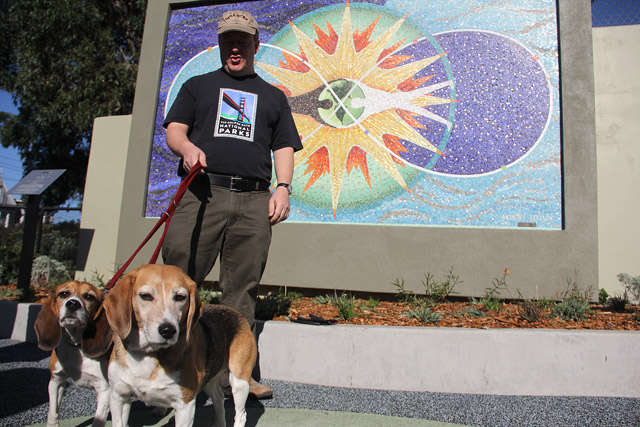 "David Schweisguth stands in front of a recently restored mural titled ""Brotherhood of Man"" in Franklin Square Park Saturday. Schweisguth's dog Huxley (right) discovered the mural rotting in the park in 2006. Photo by Dorothy M. Atkins."