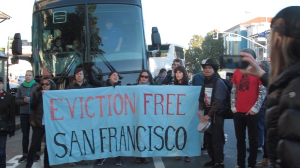 Protesters blockade an Apple shuttle bus at the Valencia St. and 24th St. Muni stop. A protester ironically takes a photo with her iPhone. Photo by Courtney Quirin.