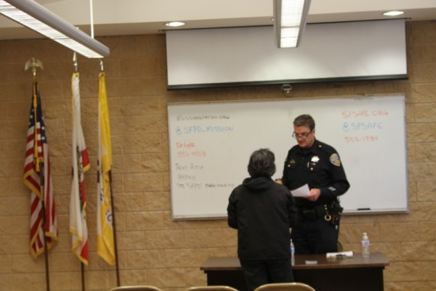Officer Steve Keith speaks to a Mission resident at Tuesday's community meeting with the police. Photo by Joe Rivano Barros