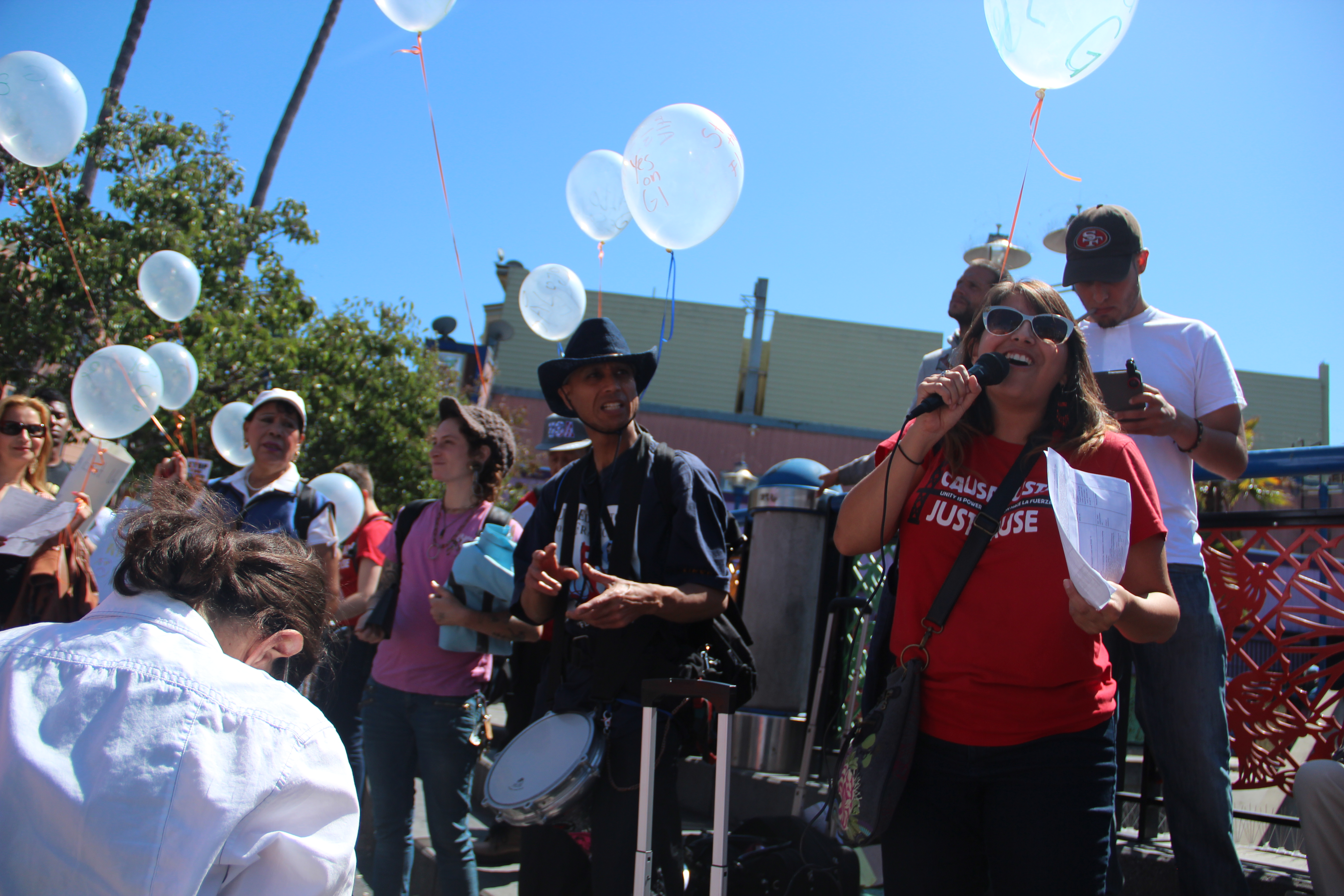 Maria Zamudio, Causa Justa Housing Rights Campaign Lead Organizer, speaks to the crowd at the 16th Street Bart Plaza on Saturday. Photo by Leslie Nguyen-Okwu.