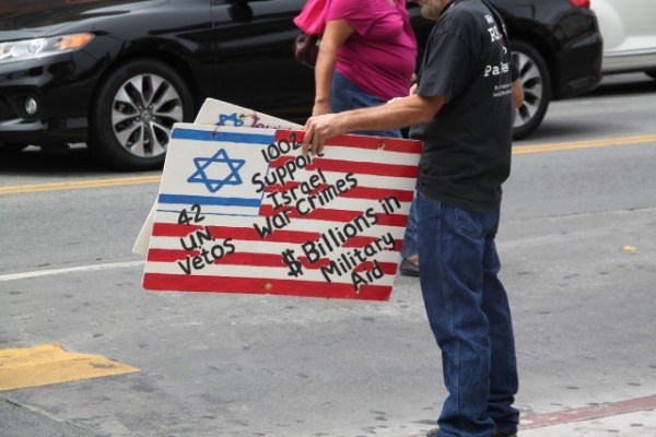 A man holding signs protesting the military aid given by the United States to Israel. Photo by Joe Rivano Barros.
