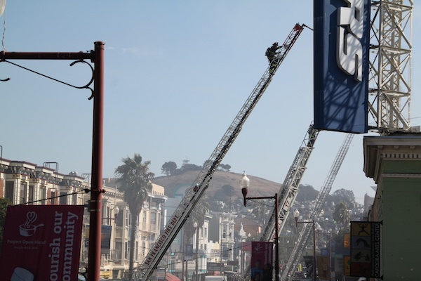 A firefighter climbs a ladder as 5-alarm fire on Mission Street wares down. Photo by Daniel Hirsch.