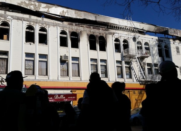 Residents of the building at 22nd and Mission look on at burnt building. Photo by Daniel Hirsch.