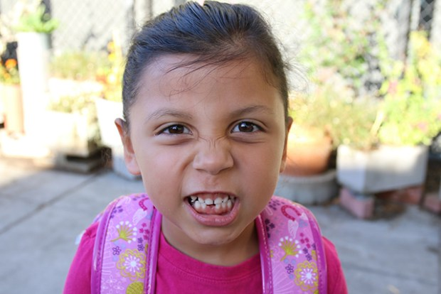 Five-year-old Natalia Lopez, on the way to school with her mom and brother, shows off the tooth she lost. The Tooth Fairy paid $3 for that tooth. Photo by Janet Kornblum