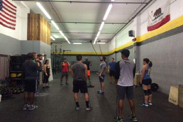 At CrossFit Alinea, Coach Pat Savage (center) is instructing members at the beginning of their workout. Photo by Laura Waxmann