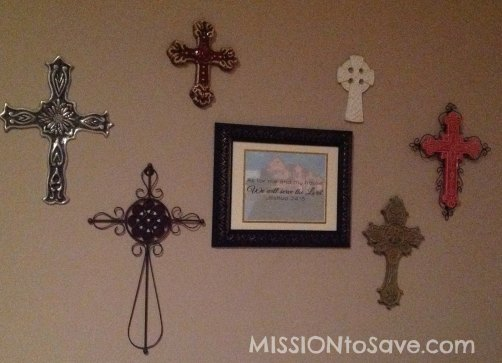 Wall display with a variety of crosses and personalized house picture.
