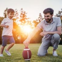 Dad playing football with his son