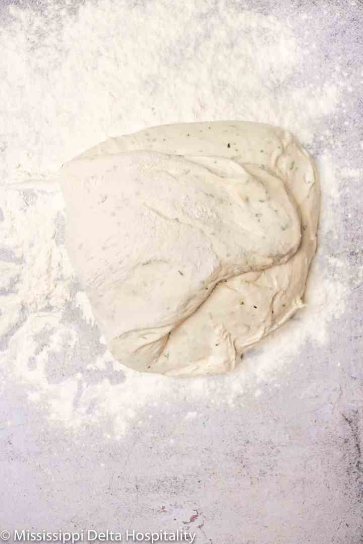 rosemary focaccia being folded on a heavily floured concrete board