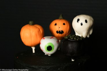 red velvet cake pops covered in modeling chocolate to look like two pumpkins, one green eye, one ghost, and one cauldron.