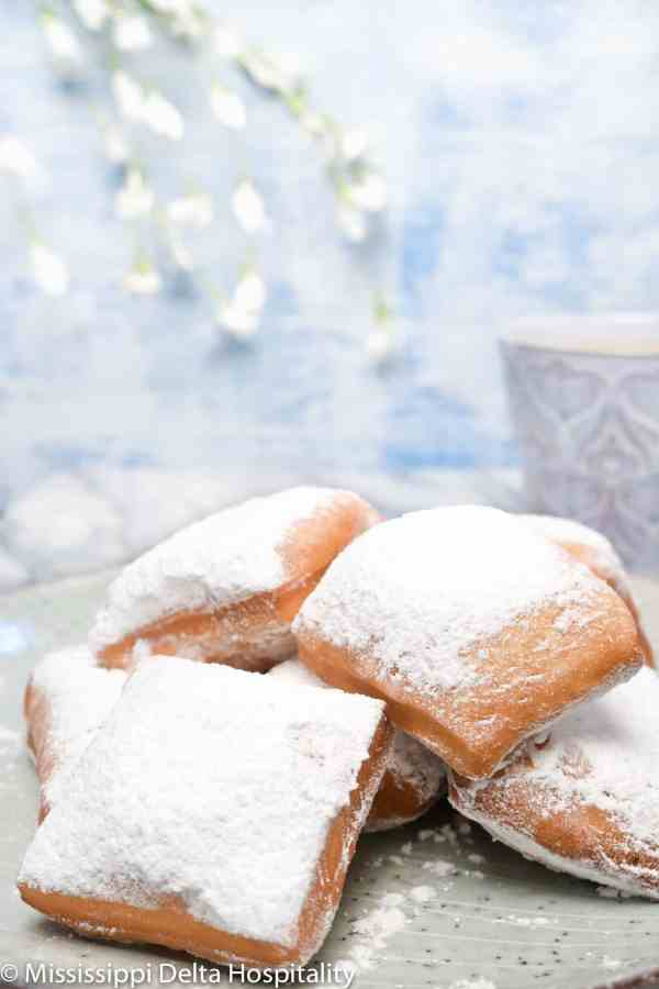 a pile of beignets on a plate with a cup of coffee on a marble board and a light blue background.
