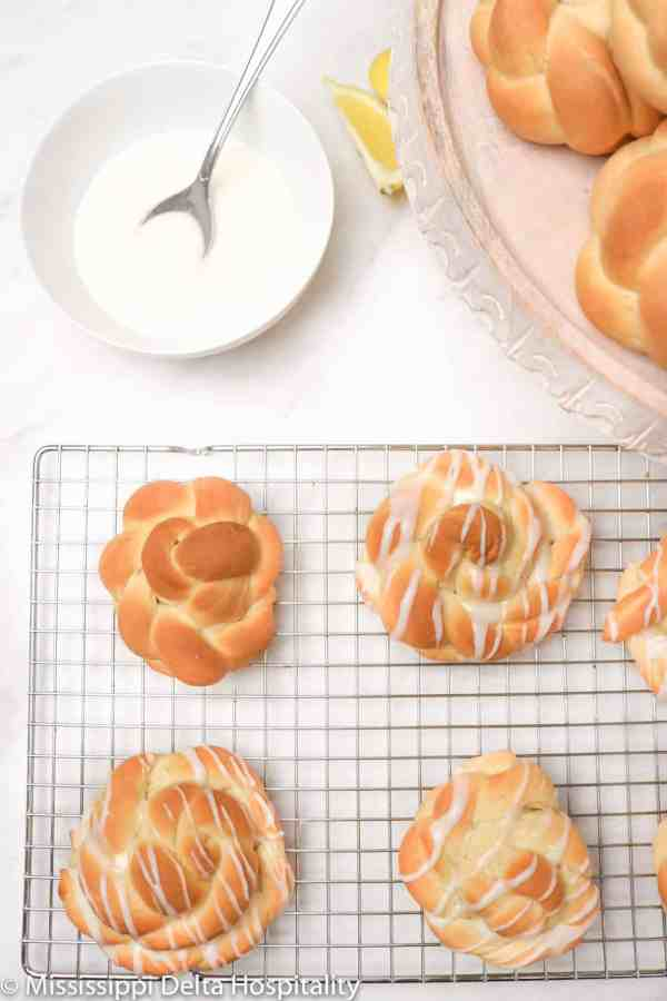 Lemon knots on a cooling rack with three of them iced and one not.