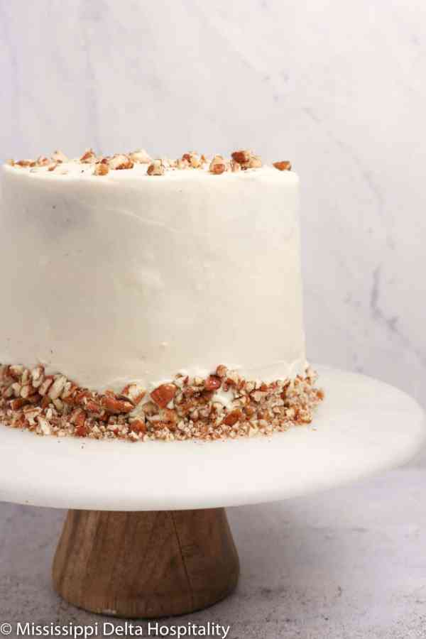 hummingbird cake on a marble cake plate with chopped pecans.