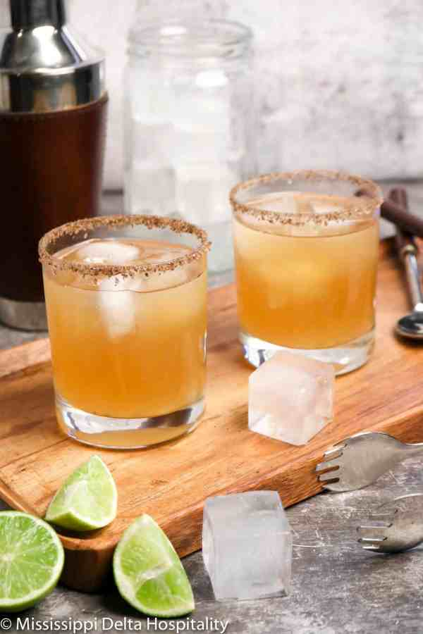two glasses of margaritas sitting on a wood board with ice and slices of lime along with a cocktail shaker, a jar of ice, tongs, and a stirrer on a concrete board.