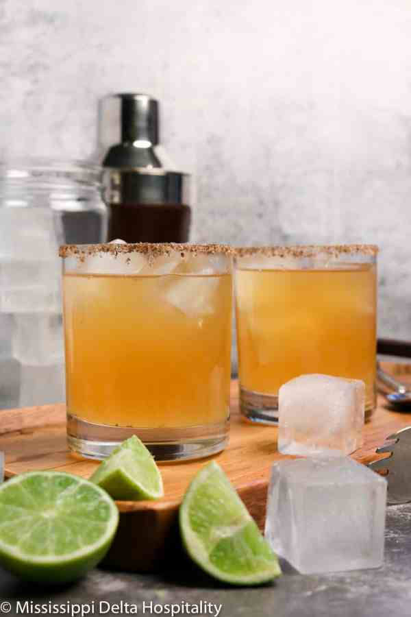 two glasses of margaritas sitting on a wood board with ice and slices of lime along with a cocktail shaker, a jar of ice, and ice tongs on a concrete board.