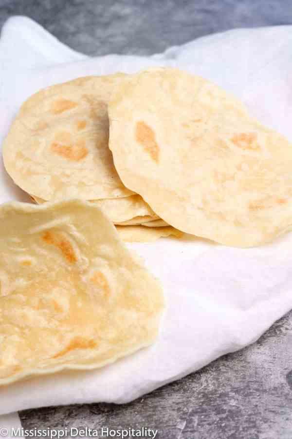 seven flour tortillas sitting on a white napkin on a concrete board